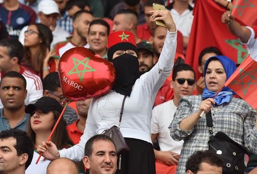رَايات حمراء لجمهور المنصة الجانبية وأجواء حماسية تسبق مباراة الغابون